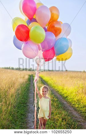 Happy Little Girl Child Kid With Balloons Outdoors On Sky And Field Background