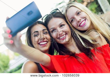 Three Friends Taking Photos With A Smartphone In The Street.