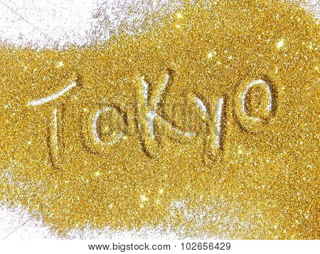 Blurry inscription Tokyo on golden glitter sparkles on white background
