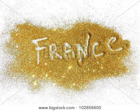 Blurry inscription France on golden glitter sparkles on white background
