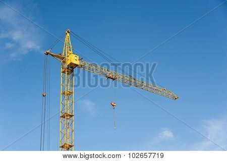 Yellow tower cranes against bright blue sky