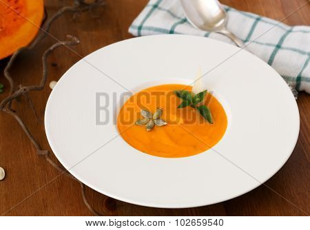 Squash Soup In A Plate With Basil Leaf