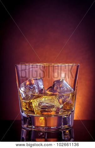 Glass Of Whiskey On Black Table With Reflection, Violet Light Tint Atmosphere