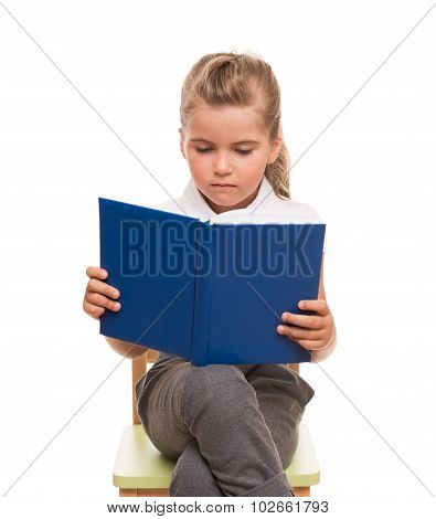 Little girl is sitting on chair and reading the book