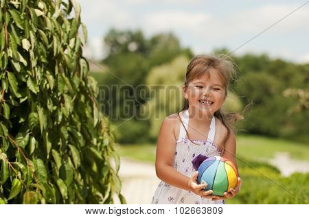 Little Girl Playing Ball In The Park