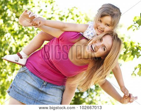 Young Mother Giving Piggyback To Her Daughter In The Park