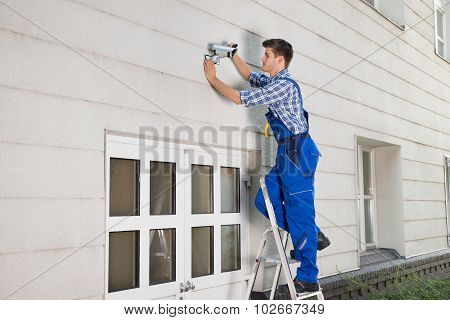 Technician Fixing Cctv Camera On Wall