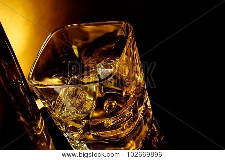 Top Of View Of Glass Of Whiskey Near Bottle On Black Table With Reflection, Warm Light