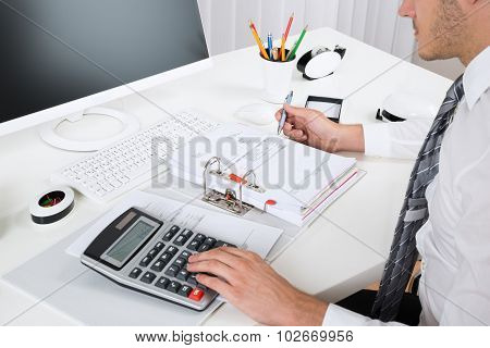 Businessperson Calculating Budget At Desk
