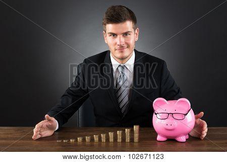 Businessman Protecting Coins And Piggybank