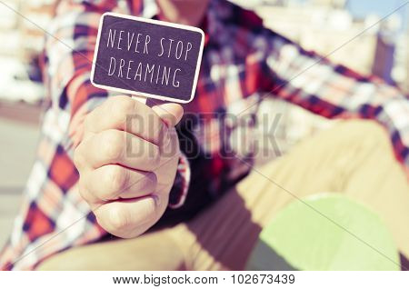 closeup of a young skater man showing a signboard with the text never stop dreaming