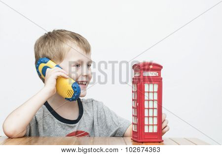 Boy Talking On The Phone And Red Telephone Booth