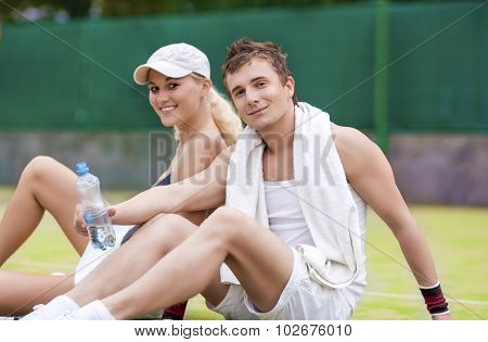 Sport And Fitness Concepts: Happy Caucasian Couple In Tennis Gear Posing On Court During Waterbrake