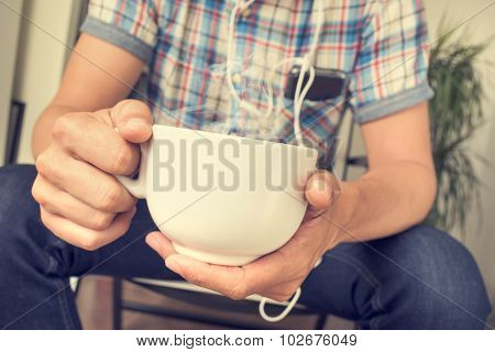 closeup of young caucasian man having a cup of coffee or tea and listening to music form his smartphone