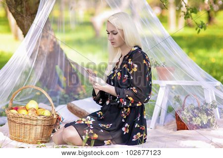 Blond Caucasian Woman Using Ebook Tablet Reader Outside In Forest. Relaxing Time With Big Basket Ful