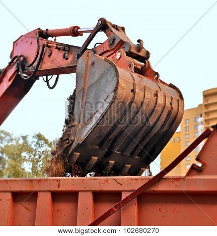 The Bucket Of The Excavator Filling Sand In A Truck Body