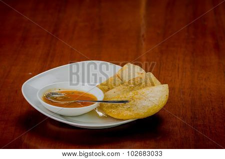 White plate with three delicious empanadas lined up and small bowl of red salsa on top
