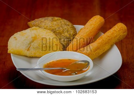 Mixed white plate of typical latin food including empanadas and a salsa bowl
