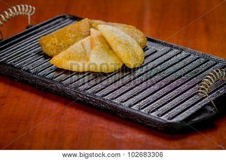 Five empanadas lying in fan formation on black metal grill tablet