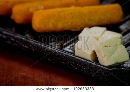 Closeup of empanadas, corn, cheese lying on black metal grill tablet