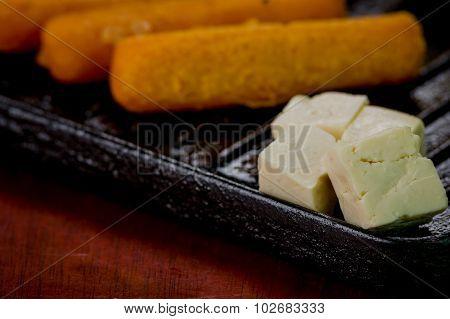 Closeup of empanadas, corn, cheese lying on black metal grill tablet