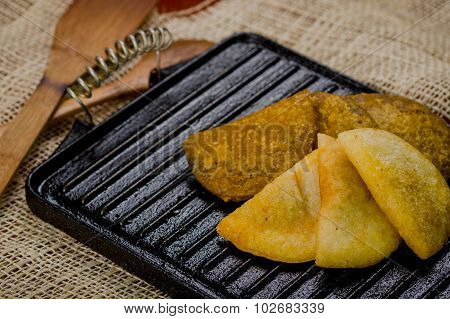 Closeup five empanadas lying in fan formation on black metal grill tablet