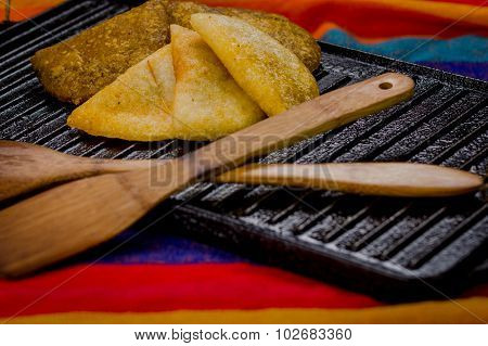 Closeup five beautifully colored empanadas lying in fan formation on black metal grill tablet with w