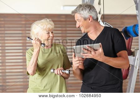 Senior woman exercising with dumbbells in gym and instructor holding tablet PC