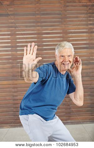 Old smiling man dancing in a fitness center
