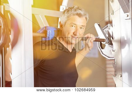 Man doing weightlifting in gym with barbell in summer