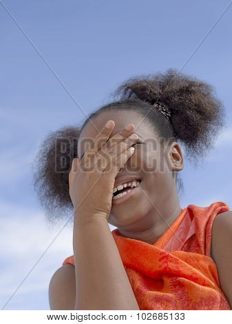 Afro girl with pigtails laughing, ten years old