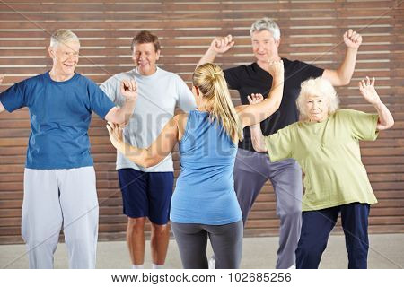 Dancing class with happy senior people in a gym