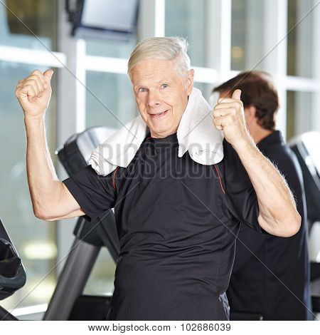 Old man on treadmill in fitness center holding his thumbs up