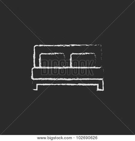 Sofa hand drawn in chalk on a blackboard vector white icon isolated on a black background.