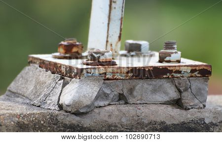 rust base plate with rust bolt on broken concrete