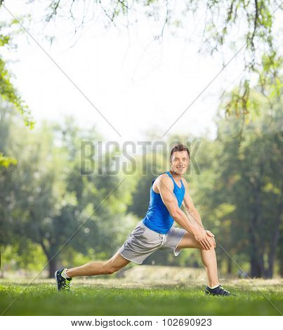Young athlete stretching his legs in a park and looking at the camera shot with tilt and shift lens