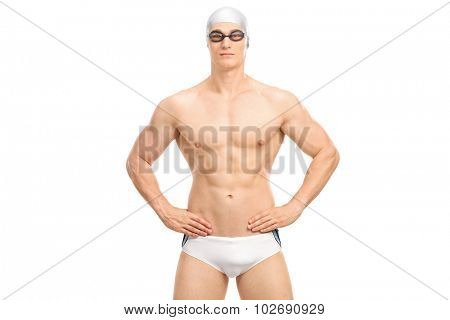 Handsome young swimmer in white swim trunks and black swimming goggles isolated on white background