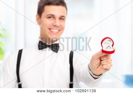 Elegant young man proposing with an engagement ring at home with the focus on the ring