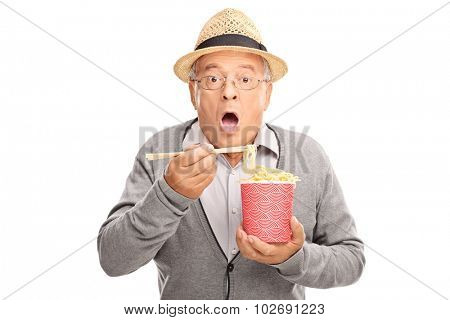 Baffled senior gentleman eating Chinese food with sticks and looking at the camera isolated on white background