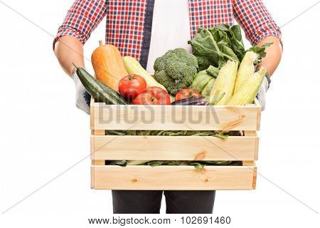 Close-up on a man holding a wooden crate full of fresh vegetables isolated on white background