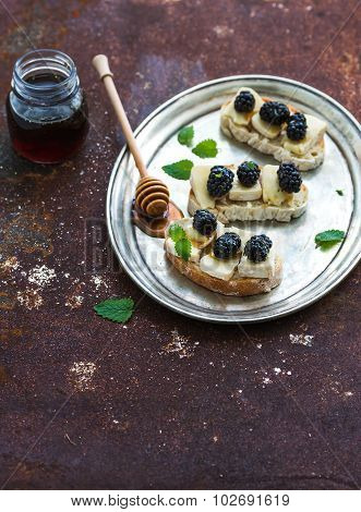 Italian bruschetta sandwich with brie cheese, honey and blackberry on vintage silver tray over grung