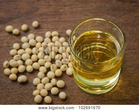 Soy oil and soy bean on wooden table.