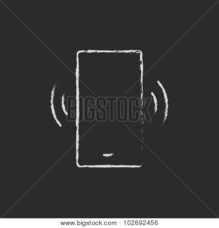 Vibrating phone hand drawn in chalk on a blackboard vector white icon isolated on a black background.