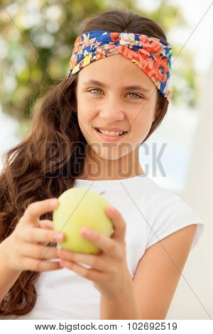 Teenager girl with blue eyes eating a apple