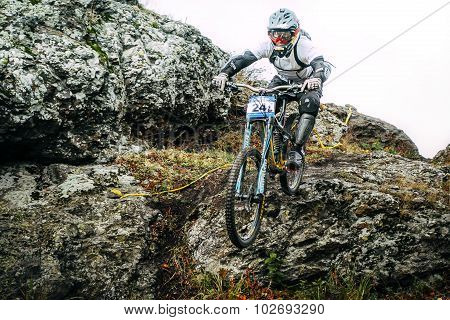 athlete at the mountain bike down the cliff