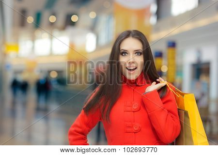 Amazed Girl in a Red Coat Shopping in a Mall