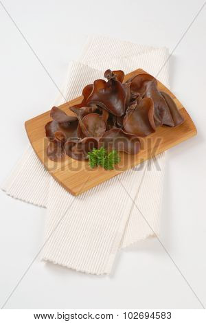 heap of cooked ear mushrooms on wooden cutting board and white place mat