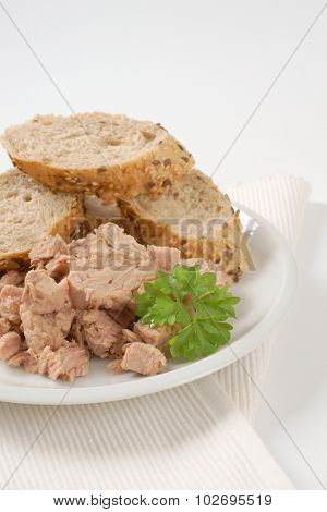 plate of tuna chunks and wholegrain bread on white place mat