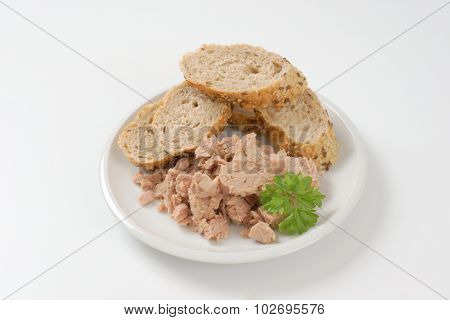 plate of tuna chunks and wholegrain bread on white background