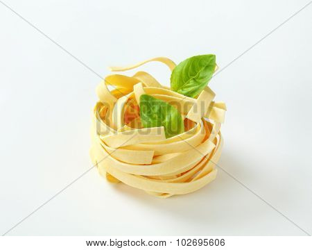 tangled piece of dry pasta decorated with green leaf